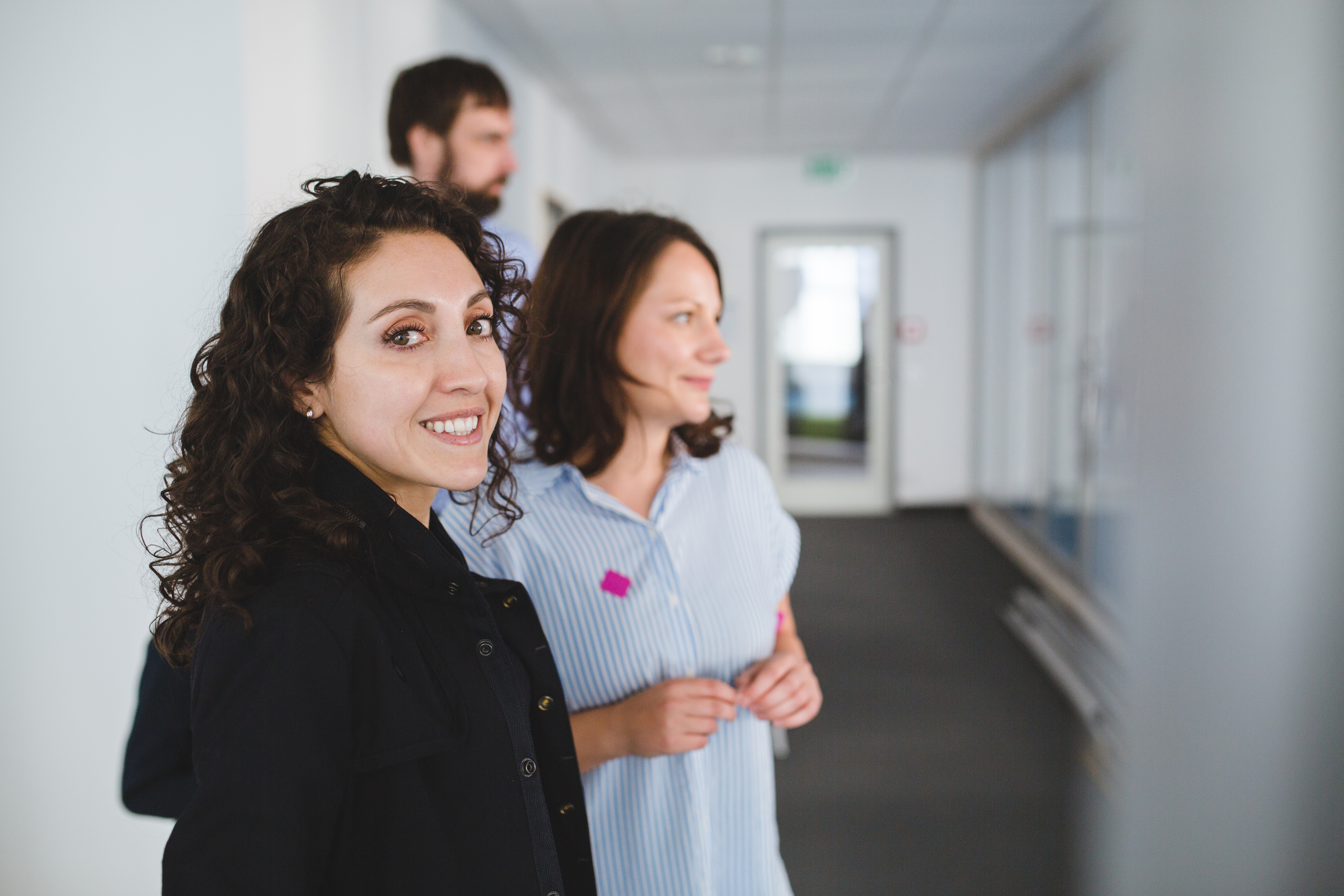 Two women and one man in a office hallway