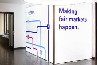 "Photo of a glowing stand up display with the copy ""Making fair markets happen."""